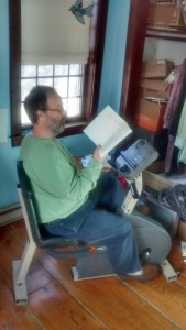Shel reading at the exercise bike. Photo by D. Dina Friedman