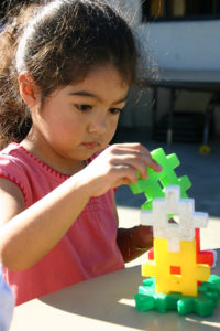 Preschool girl with a creative project. Photo by Anissa Thompson.