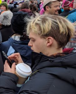 The writer's son checking his phone (at the Women's March in Washington, January 21, 2017)